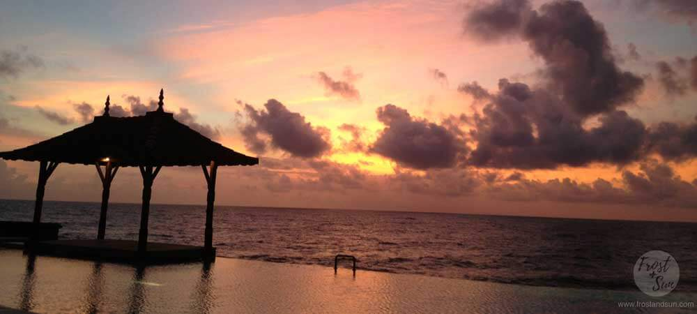 Landscape view of a yoga platform over an infinity pool overlooking the Indian Ocean during sunset.