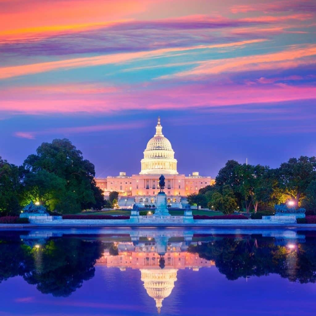 Photo of the US Capitol from the reflecting pool during sunset.