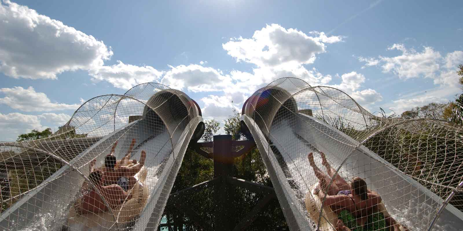 Two adults prepare to head down the Crush n Gusher water slides at Typhoon Lagoon water park.