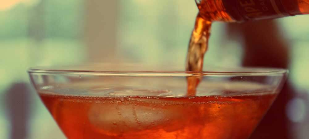 Liquor pouring into a cocktail glass