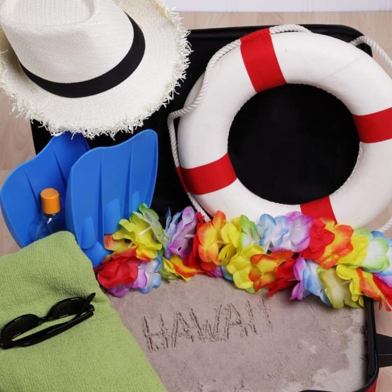 """Photo of an open suitcase filled with sand with """"Hawaii"""" written in it. Surrounding it are sunglasses, a faux lei, a straw hat, a beach towel, and other items to pack."""