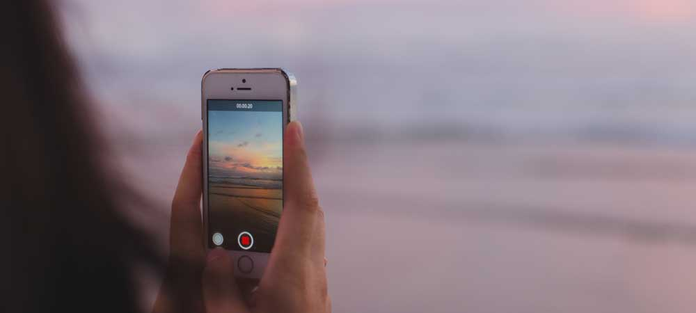 Person holding an iPhone while recording a video of a beach sunset.