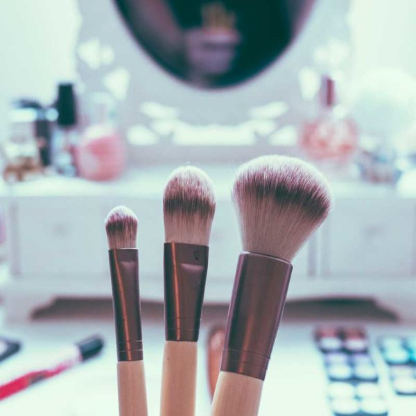Closeup of a makeup brushes with a vanity in the background.