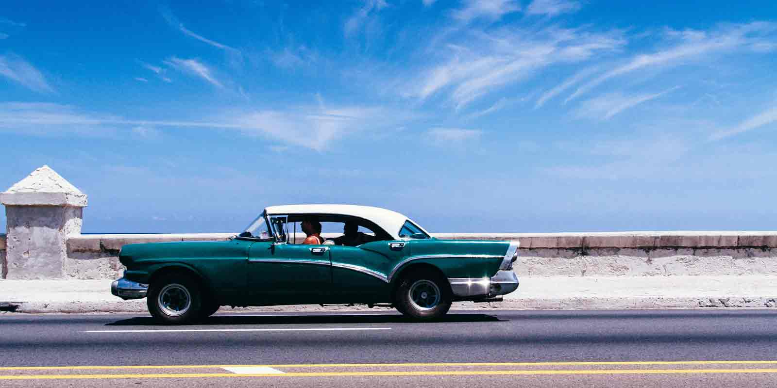 A classic car driving the coast of Cuba, a common site.
