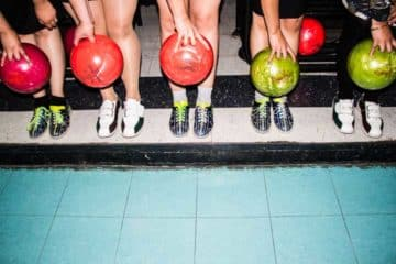 Close up of 5 people holding red and lime green bowling balls