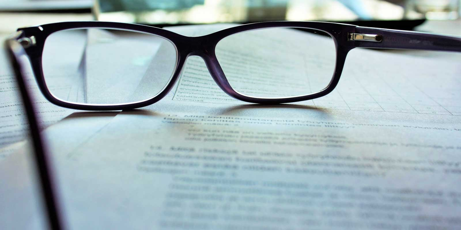 Closeup of eyeglasses sitting on top of a printed piece of paper.