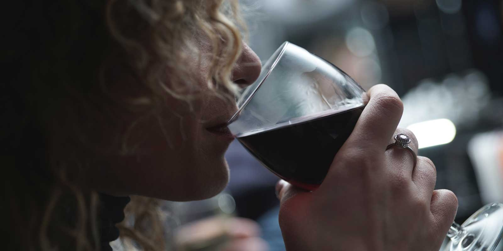 Closeup photo of a woman drinking a glass of red wine