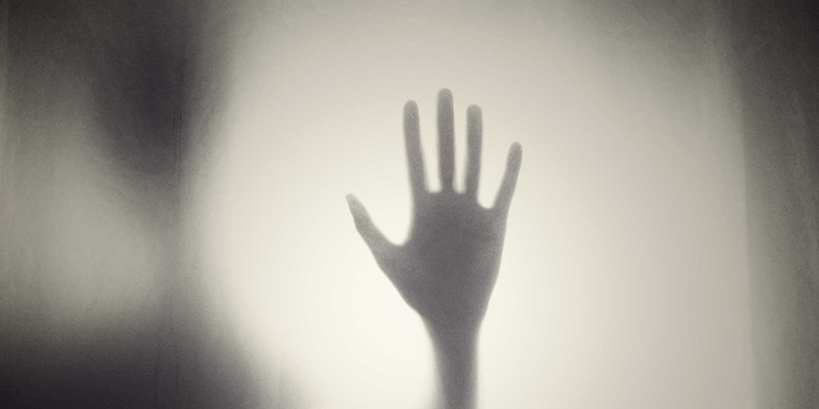 Black and white photo showing a shadow of a single hand