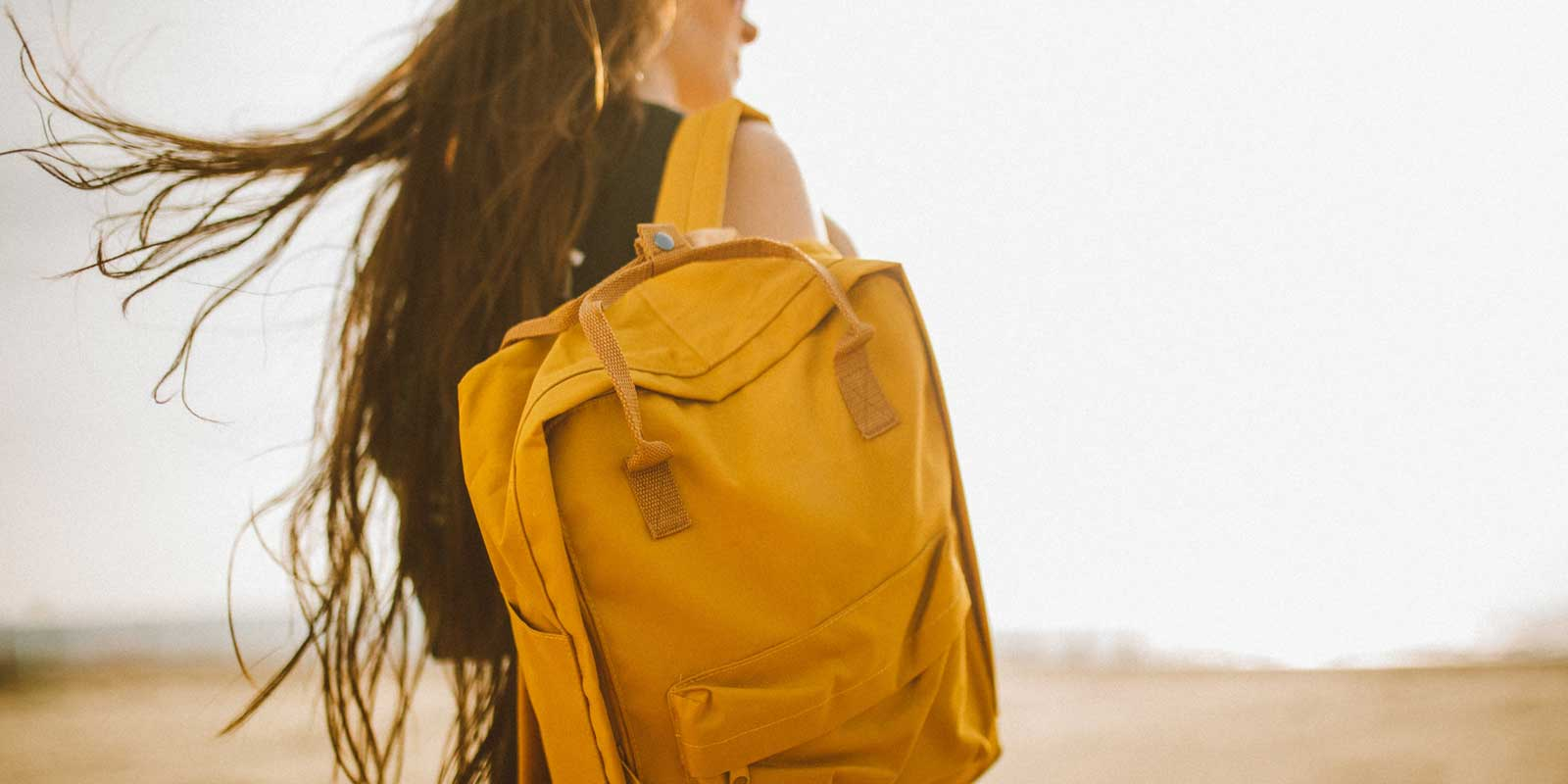 Close up of a woman carrying a mustard yellow backpack