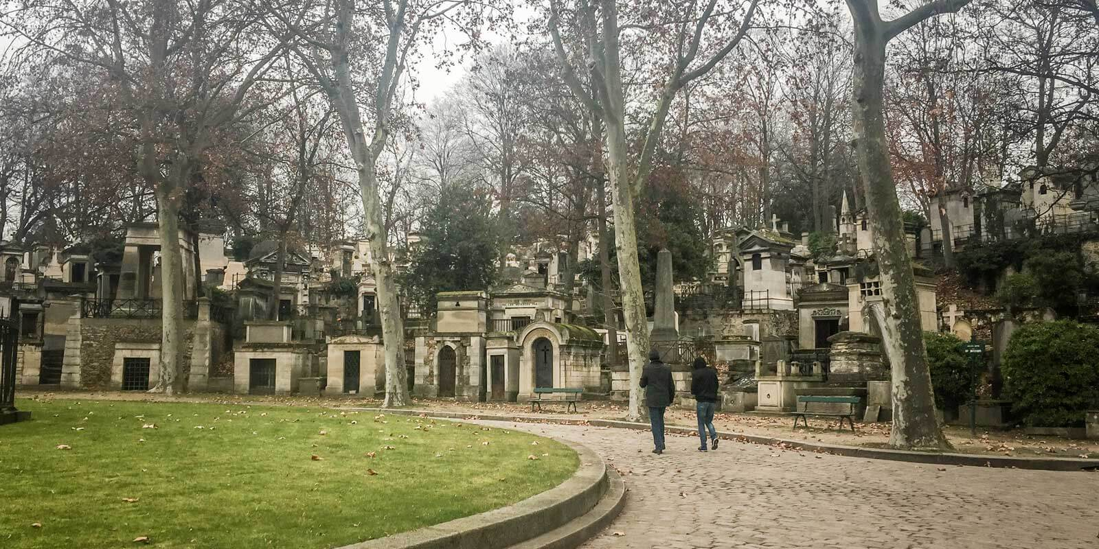 Two people walking through the hauntingly beautiful Père Lachaise cemetery in Paris on a gloomy day.
