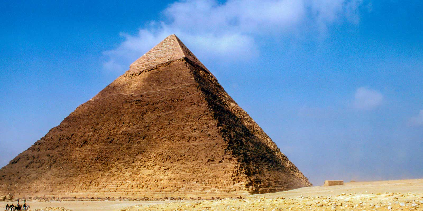 Great Pyramid in Egypt against a bright blue sky.