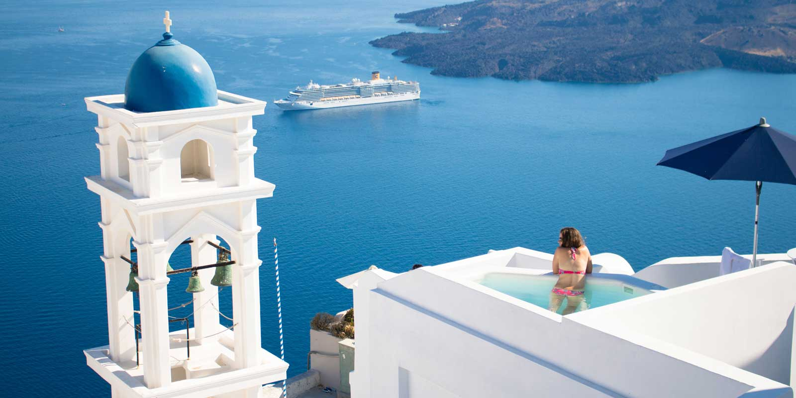 Ocean landscape view of Santorini, Greece showing a white bell tower with a blue dome, a woman in a rooftop pool, and a cruise ship in the distance.