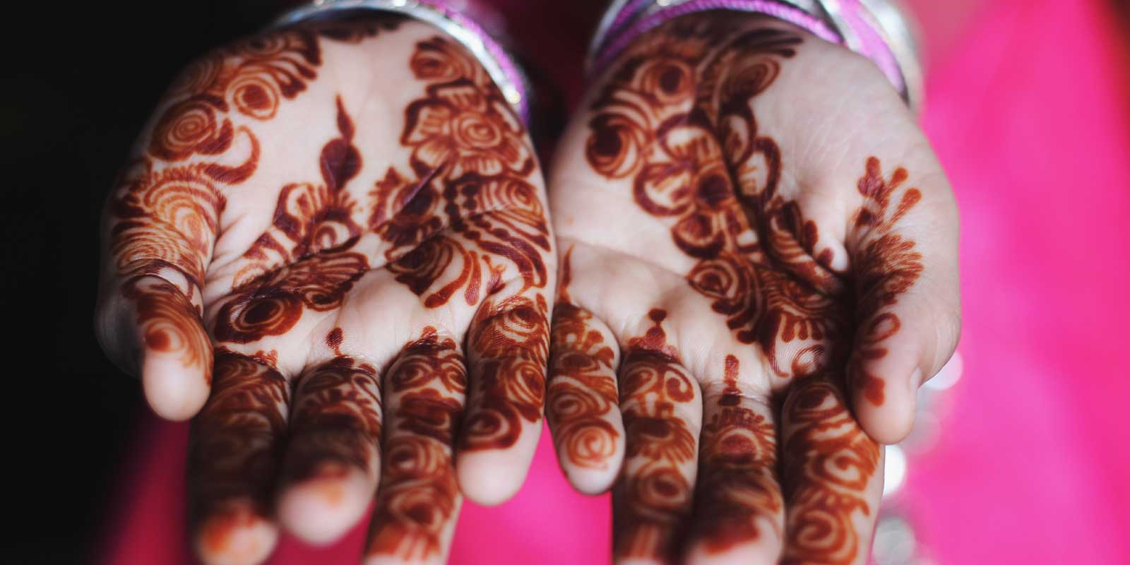 Closeup photo of a woman's hands with intricate henna tattoo on her palms.