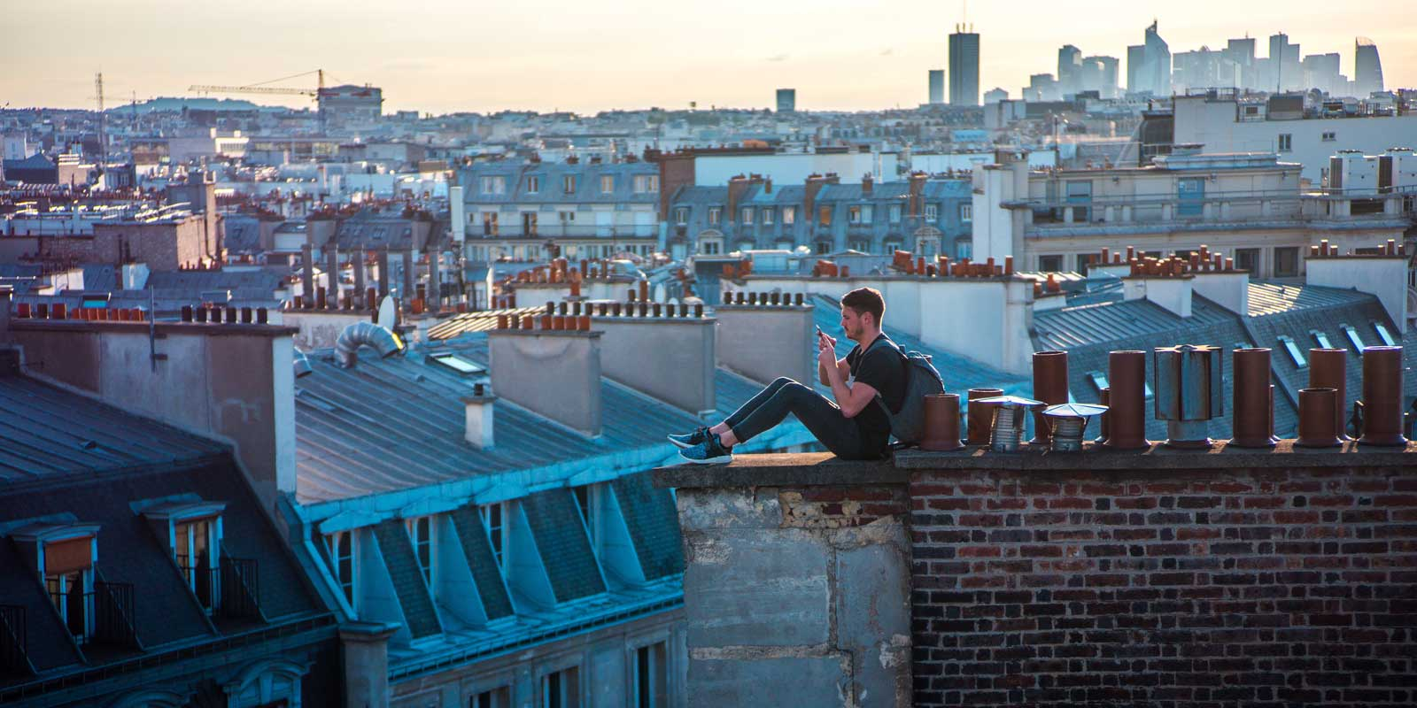Man sits on the rooftop of a building in Paris.