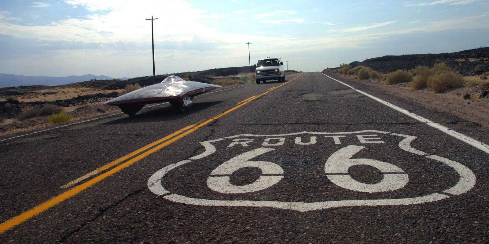 An oddly shaped solar vehicle drives down Route 66, which is painted on the pavement.