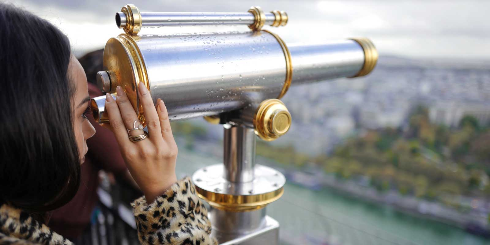 Woman looking through a telescope from the Eiffel Tower.