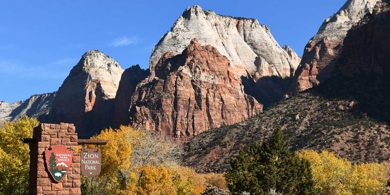 Landscape of an entrance for Zion National Park with perfect blue skies, trees with yellow and orange leaves, and rock formations in the background.