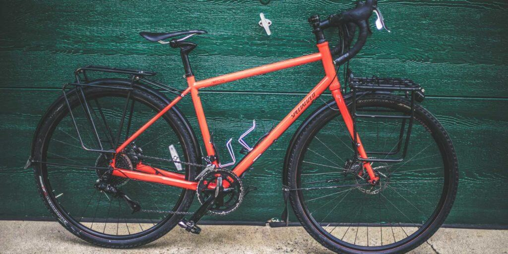 Bright orange bike set against a green wall