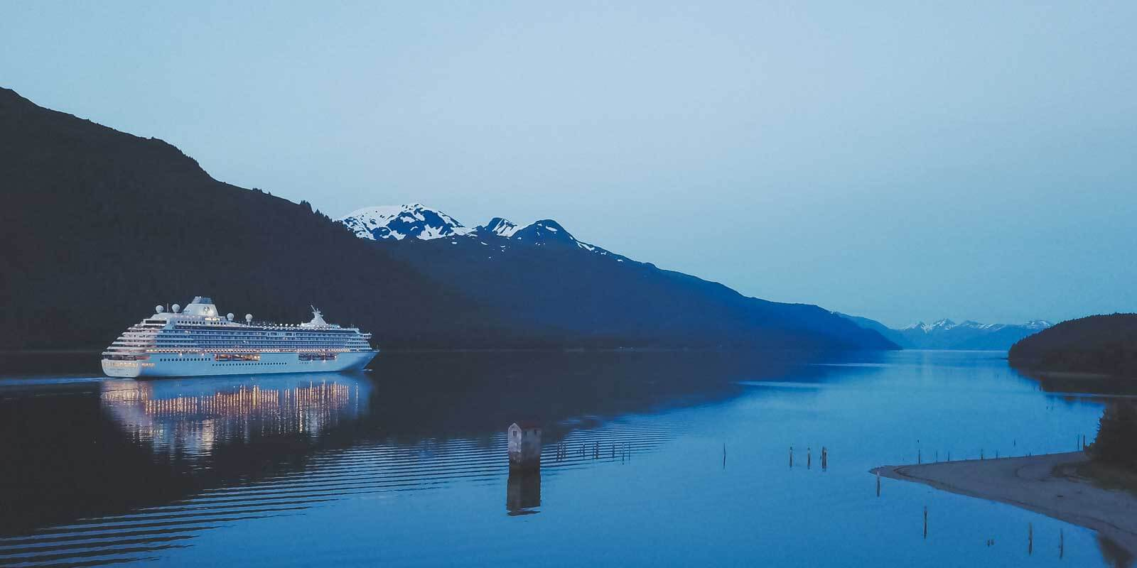 Landscape view of a cruise ship in Alaska, with snow capped mountains in the background.