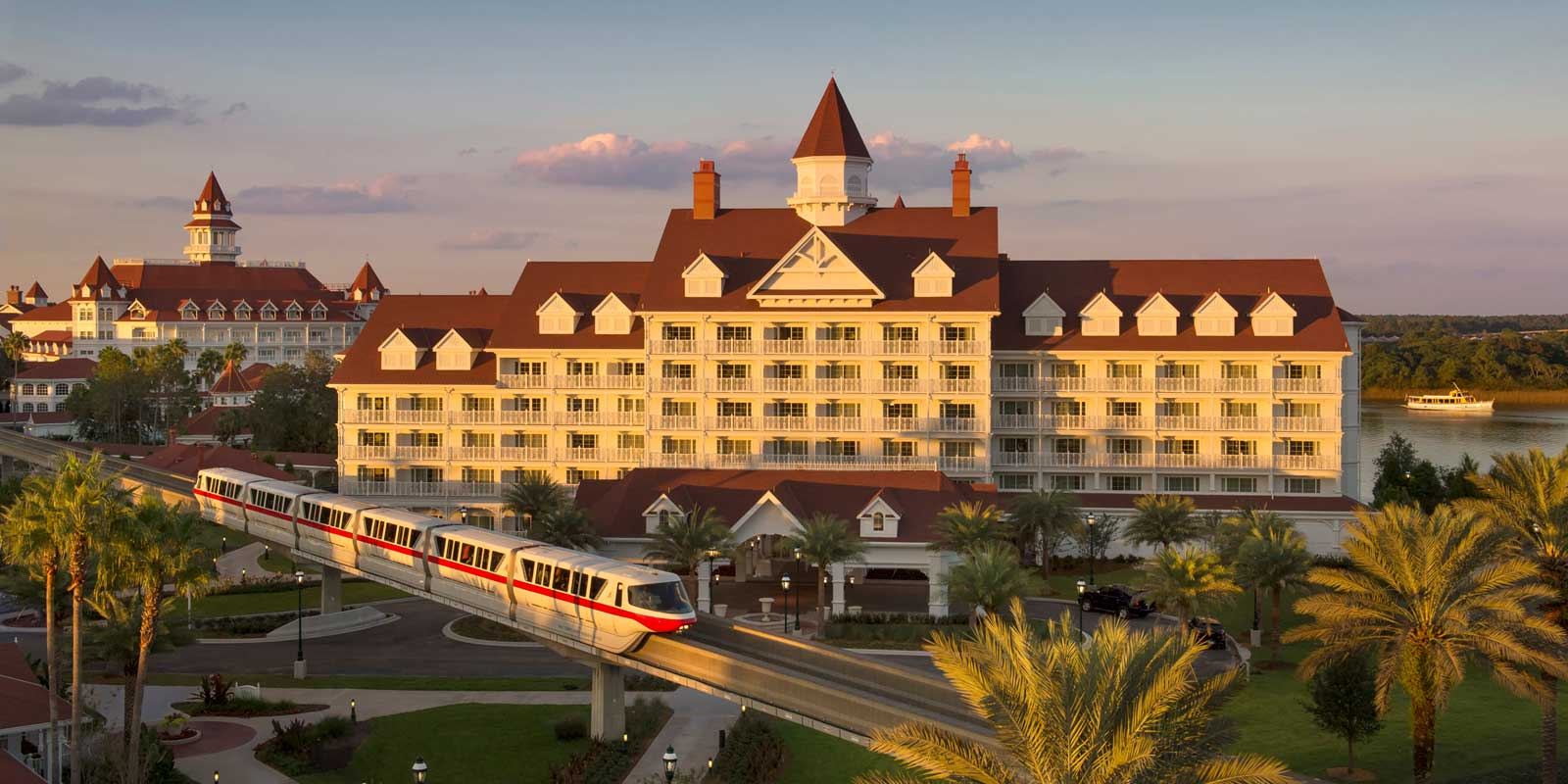 Landscape view of Grand Floridian resort at Disney World with the monorail in front and water at back.