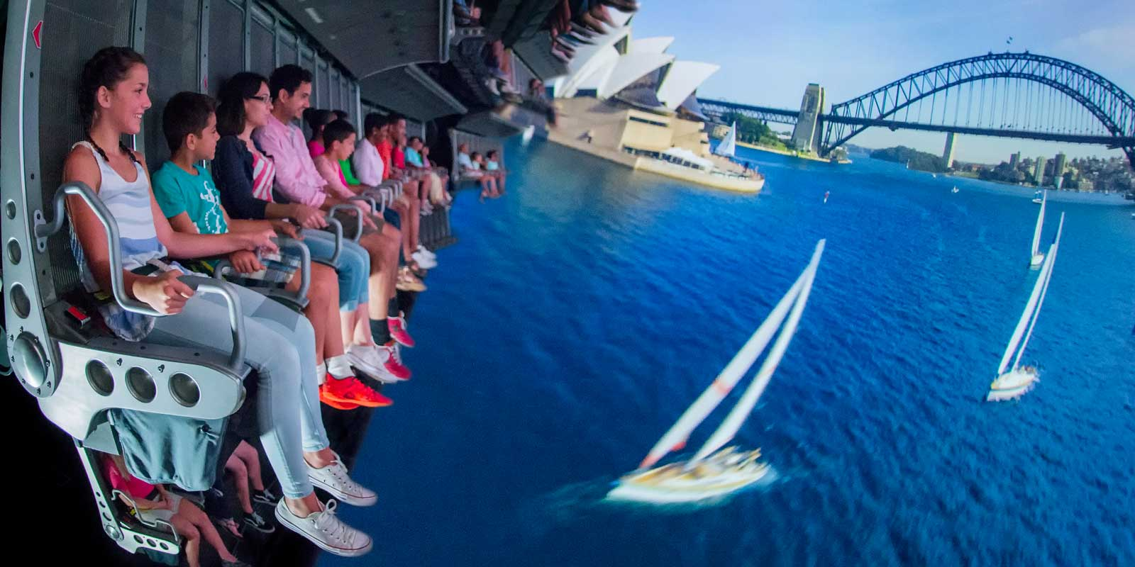 Composite photo of people enjoying Epcot's Soarin' ride, with a scene from Sydney Harbor in the foreground.