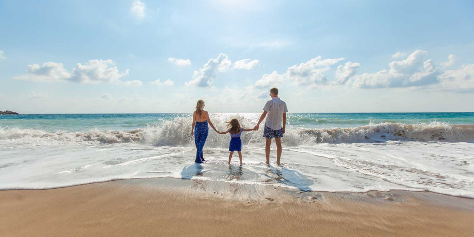 Photo of a mom, daughter, and dad holding hands at the beach.