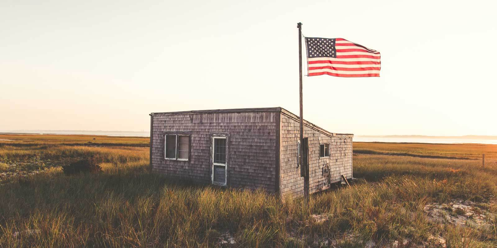American flag waves in the air next to a seaside shack in Cape Cod