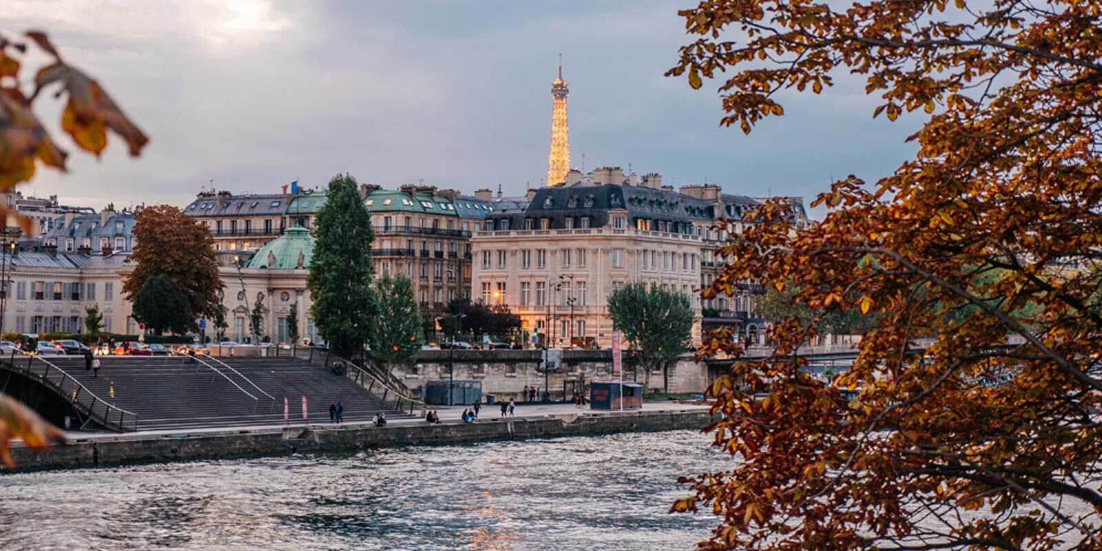 Landscape view of the Paris riverbank with the Eiffel Tower in the distance.