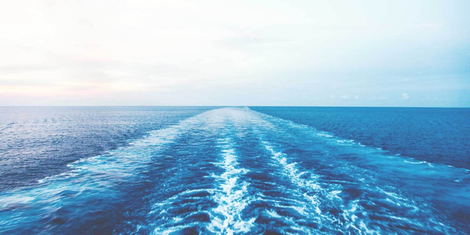 Landscape view of an open ocean with the wake trail from a cruise ship.