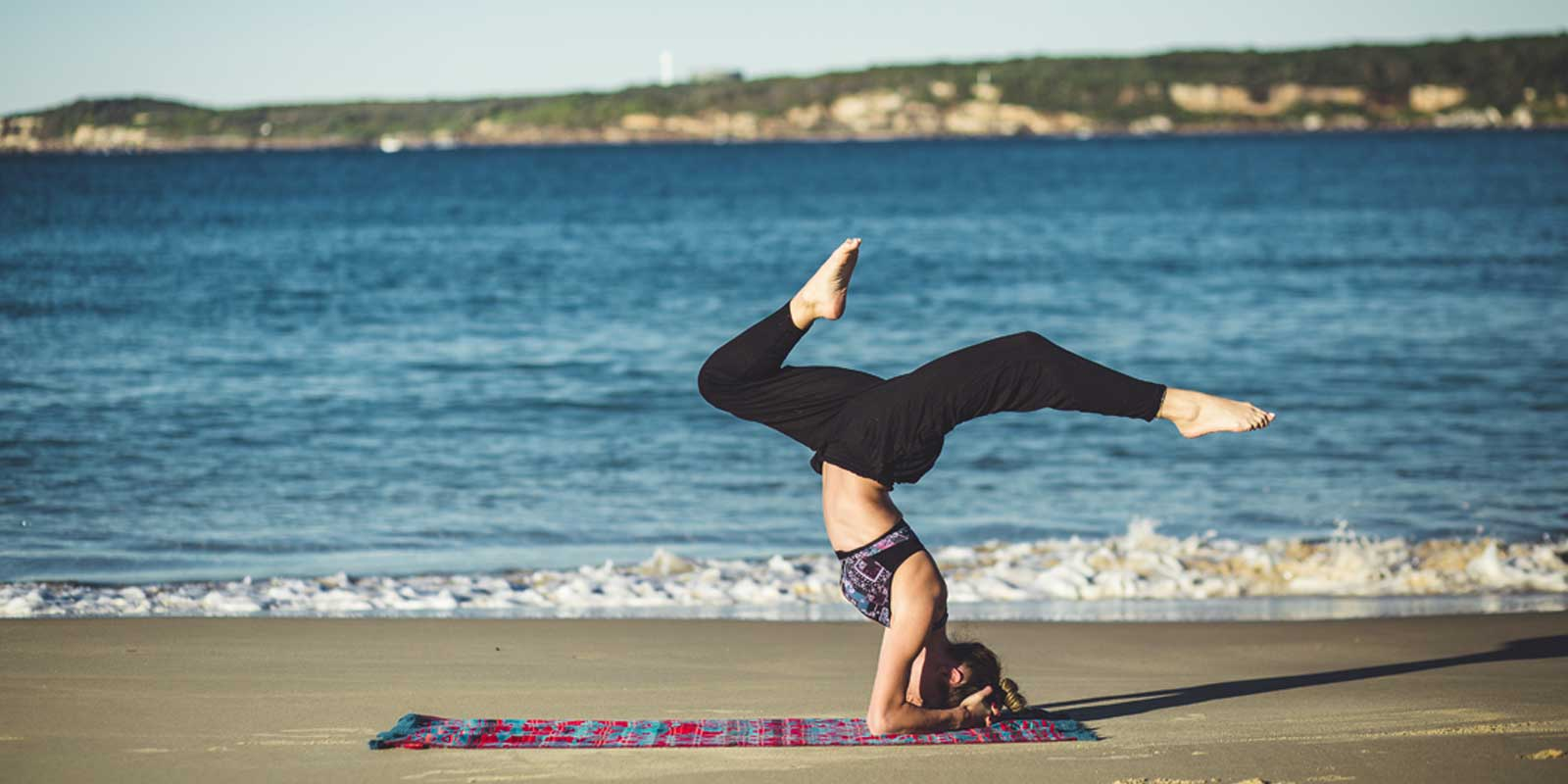 Woman doing yoga on an ocean beach.
