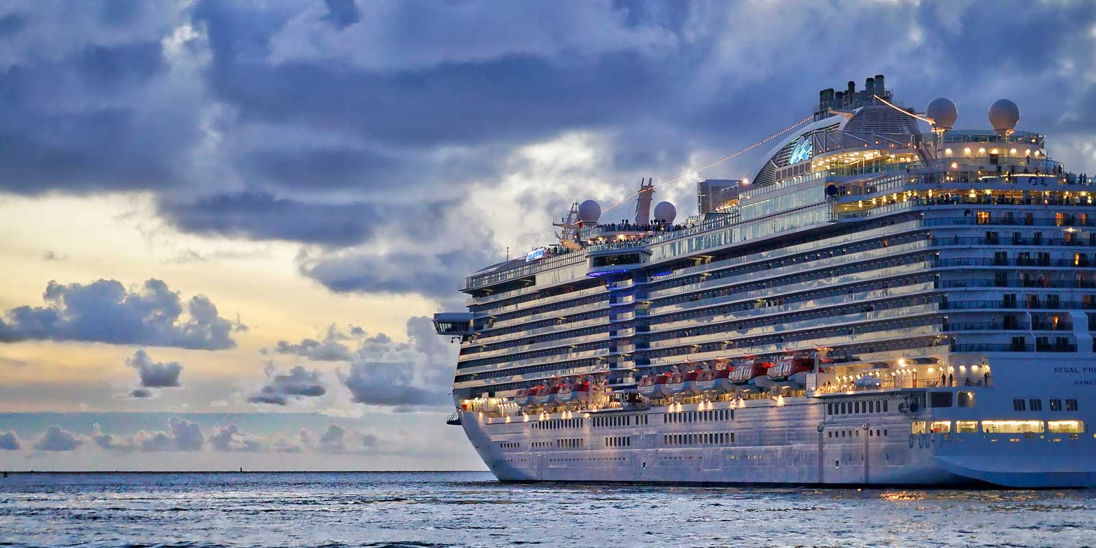 Landscape view of a gigantic vacation cruise ship at sunset.