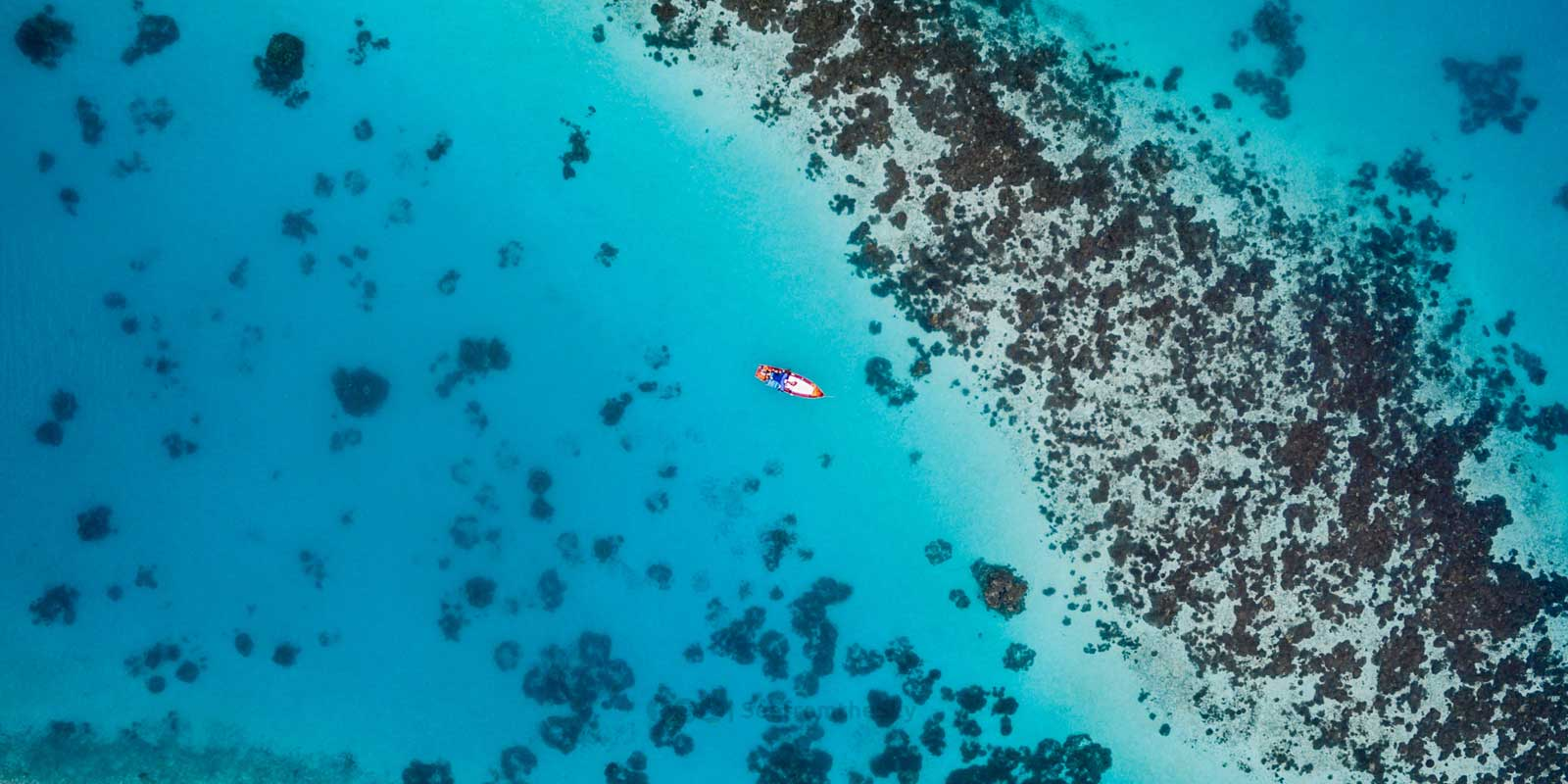 Aerial shot of coral reef near the Maldives, with an orange boat.