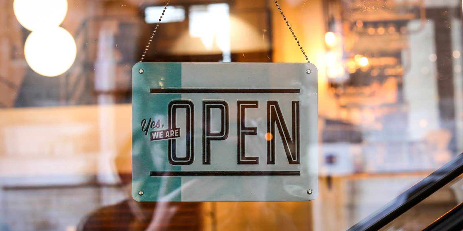 "Close up photo of a shop sign saying ""Yes, we are open."""
