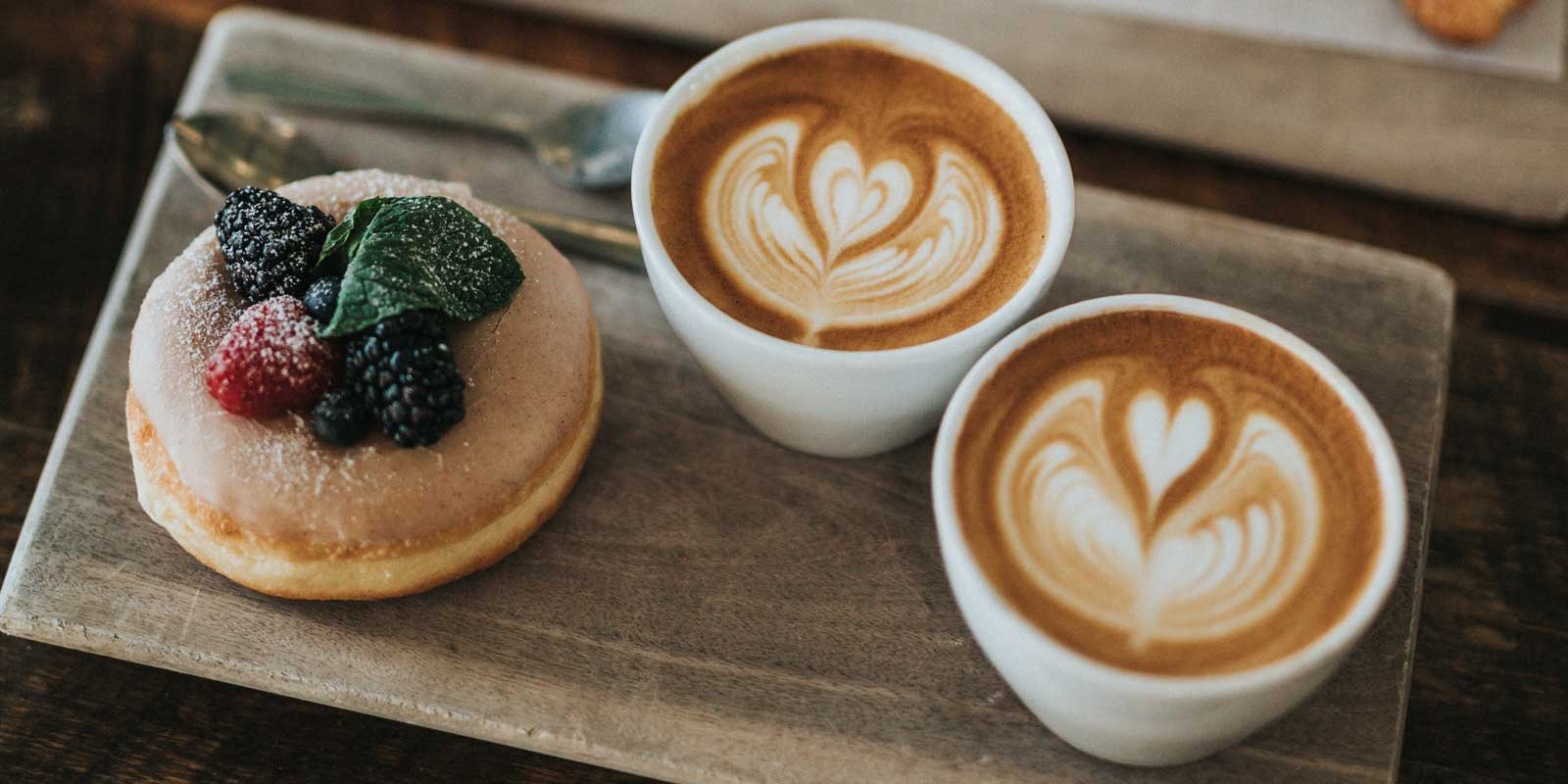 Flatlay photo of 2 cappucinos and a donut with berries on top.