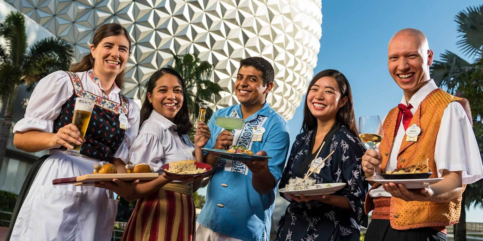 A group of 5 Disney employees holding international cuisine while dressed in international-inspired uniforms.