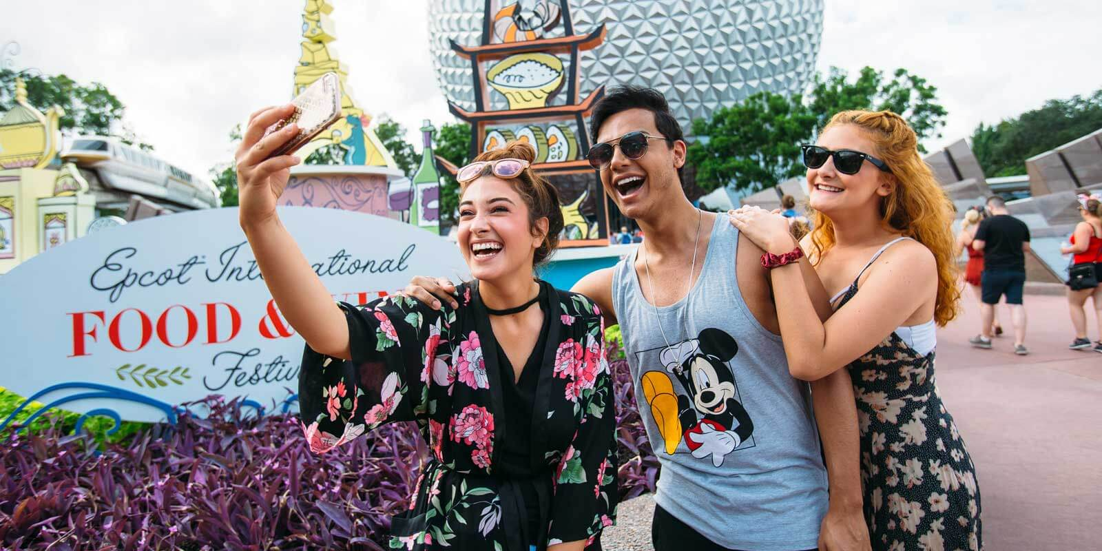A group of 3 friends stop to take a selfie at the Epcot park entrance during the Epcot Food and Wine Festival.