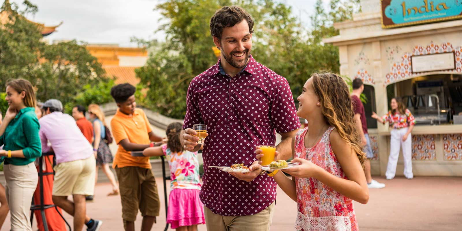 A father and daughter smile at each other while carrying a drink and plate of food at Epcot International Food & Wine Festival at Disney World in Florida.