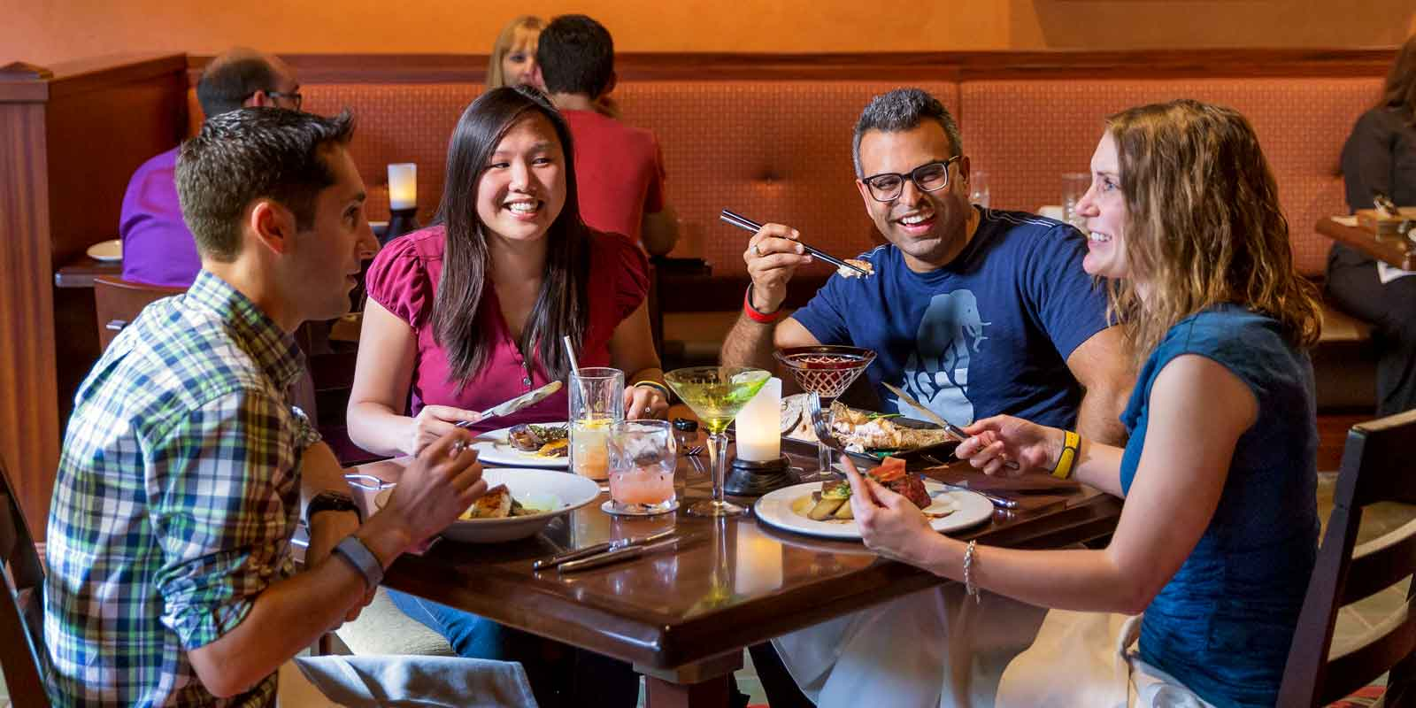 A group of adults enjoy a meal at Animal Kingdom's Tiffins restaurant.