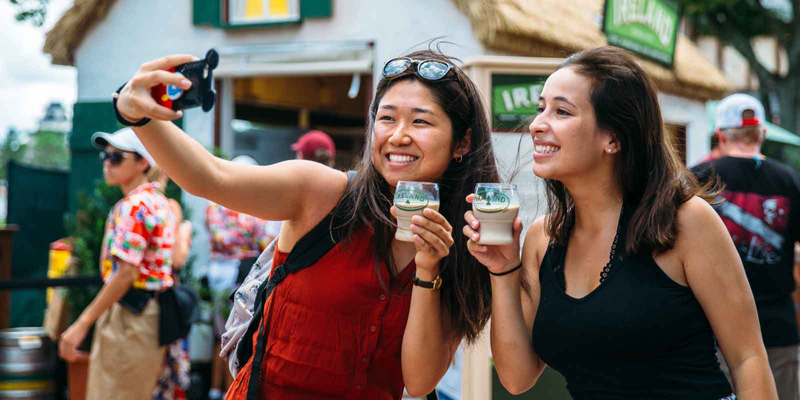 2 women pose for a selfie with a drink from the Ireland food stall at Epcot's International Food & Wine Festival.