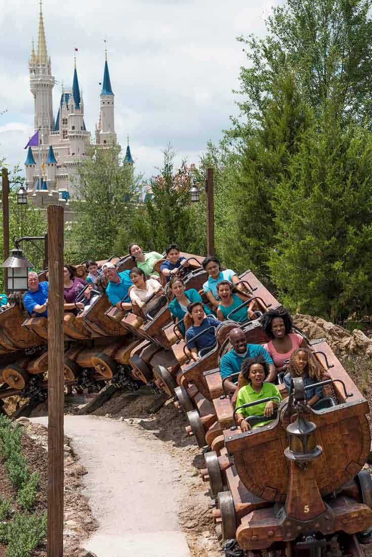 A group of people zip around a corner on the Seven Dwarfs Mine Train at Disney World's Magic Kingdom.
