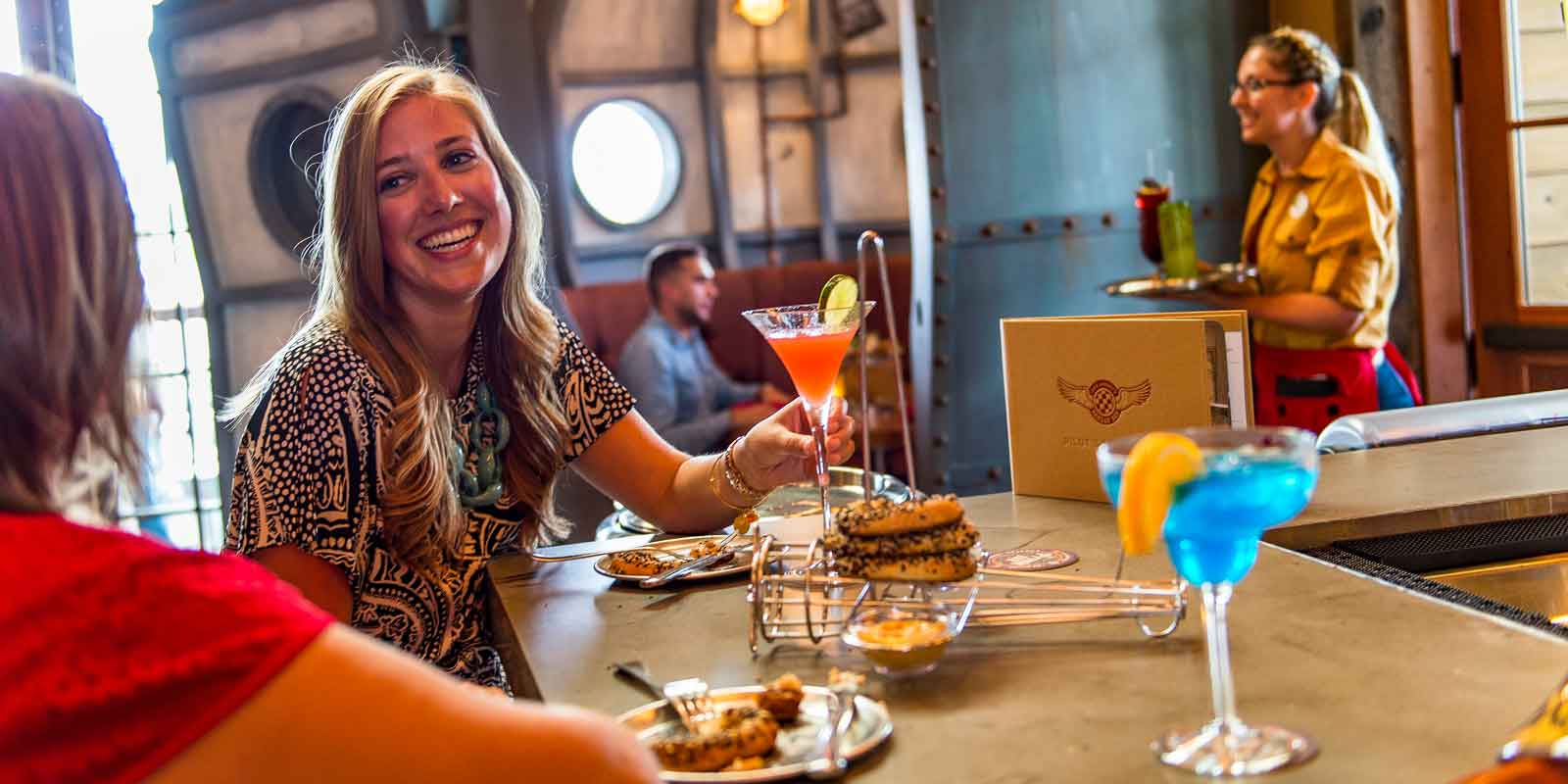 Close up of 2 women enjoying cocktails and an appetizer, with a cocktail waitress in the background, at Jock Lindsey's Hangar Bar.