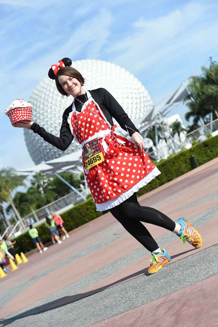 Woman dressed as Minnie Mouse and running sneakers poses in front of the Epcot sphere.