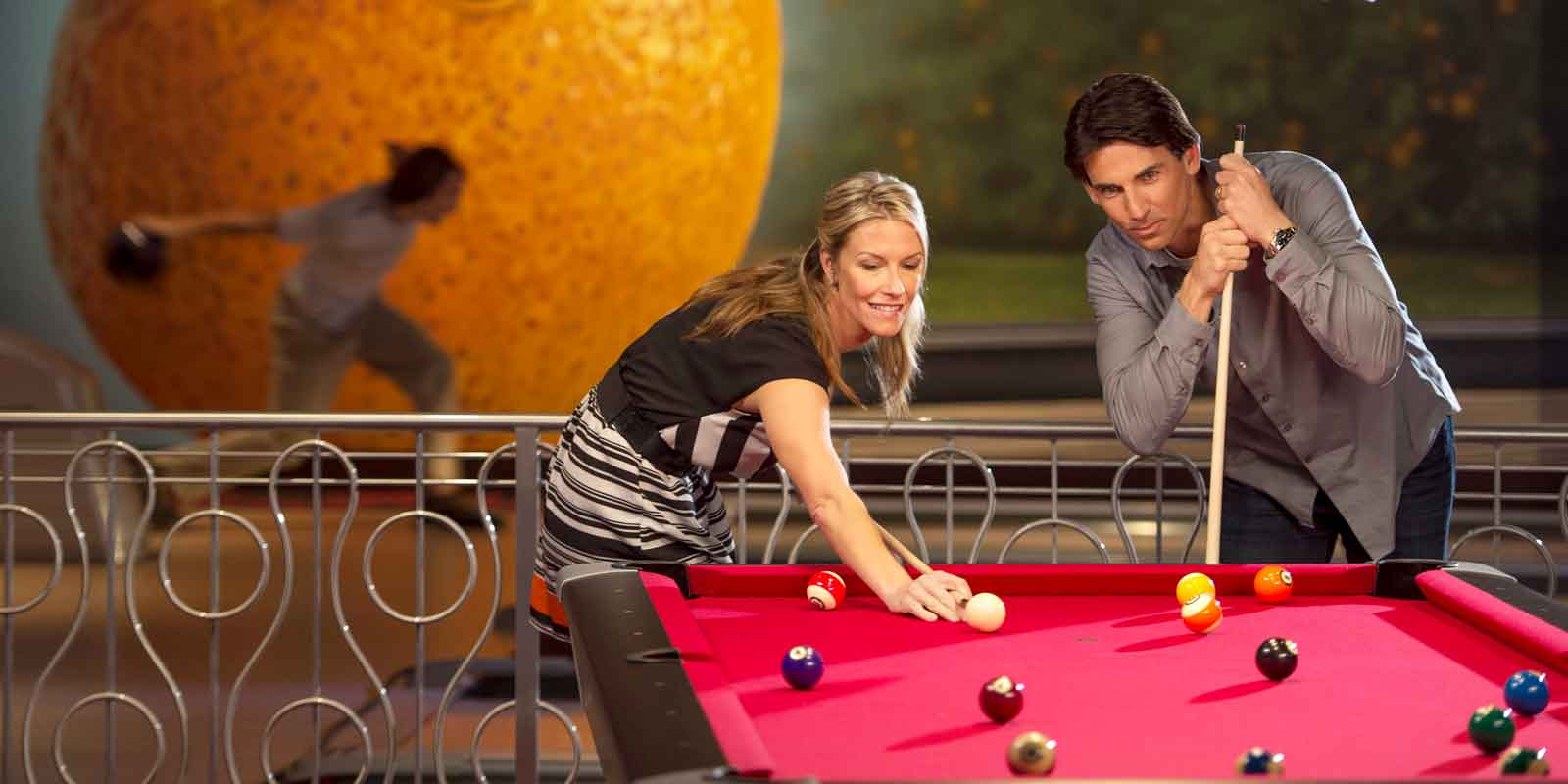 A woman and man play a game of pool on a red pool table, while a person in the background bowls.
