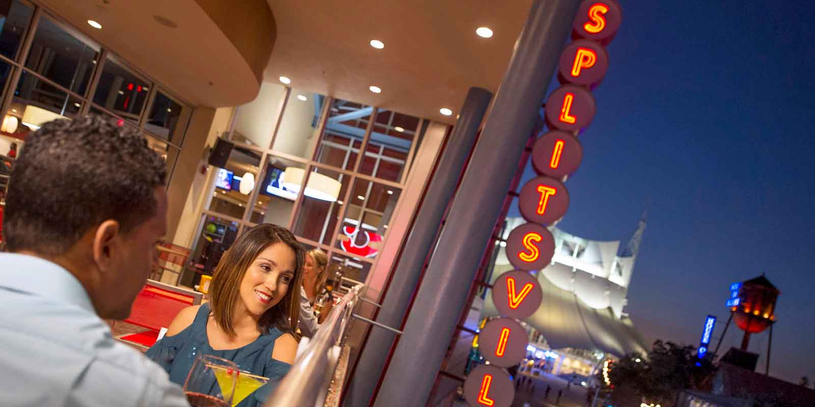 A couple sits on the outdoor deck at Splitsville in Disney Springs.