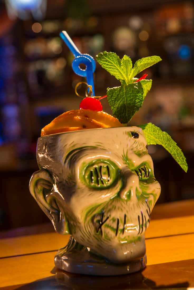 Closeup of a ceramic zombie cup filled with a cocktail and fruit, mint and a blue twisty straw.