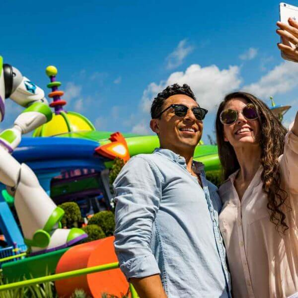 An adult couple takes a selfie in front of a giant Buzz Lightyear figure at Hollywood Studios' Toy Story Land.