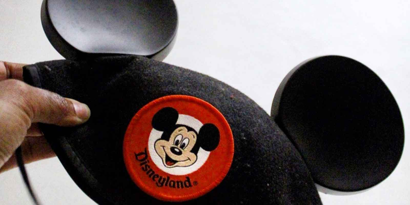 Closeup of a person holding a classic Mickey Mouse cap with a Disneyland patch on the front.