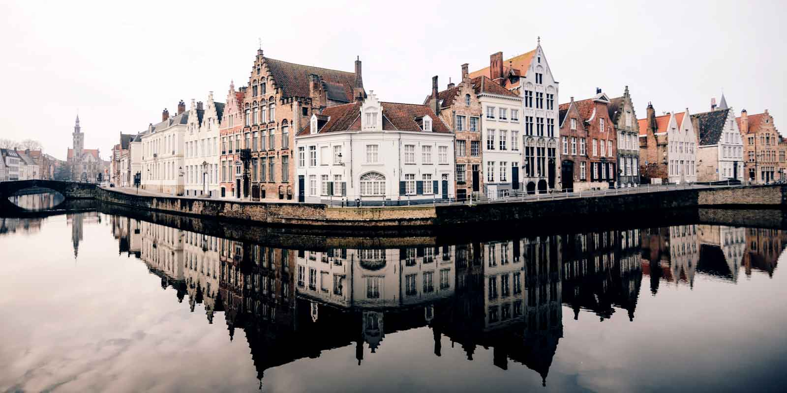 Landscape view of Bruges, Belgium from a bend in a canal, with buildings reflecting in the water.