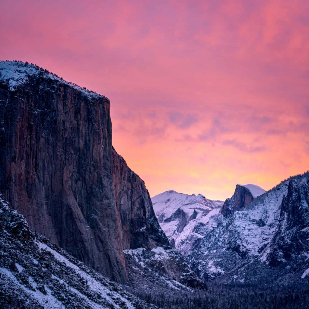 Landscape photo of a snow covered mountain in Yosemite National Park with pink skies in the backgrround.