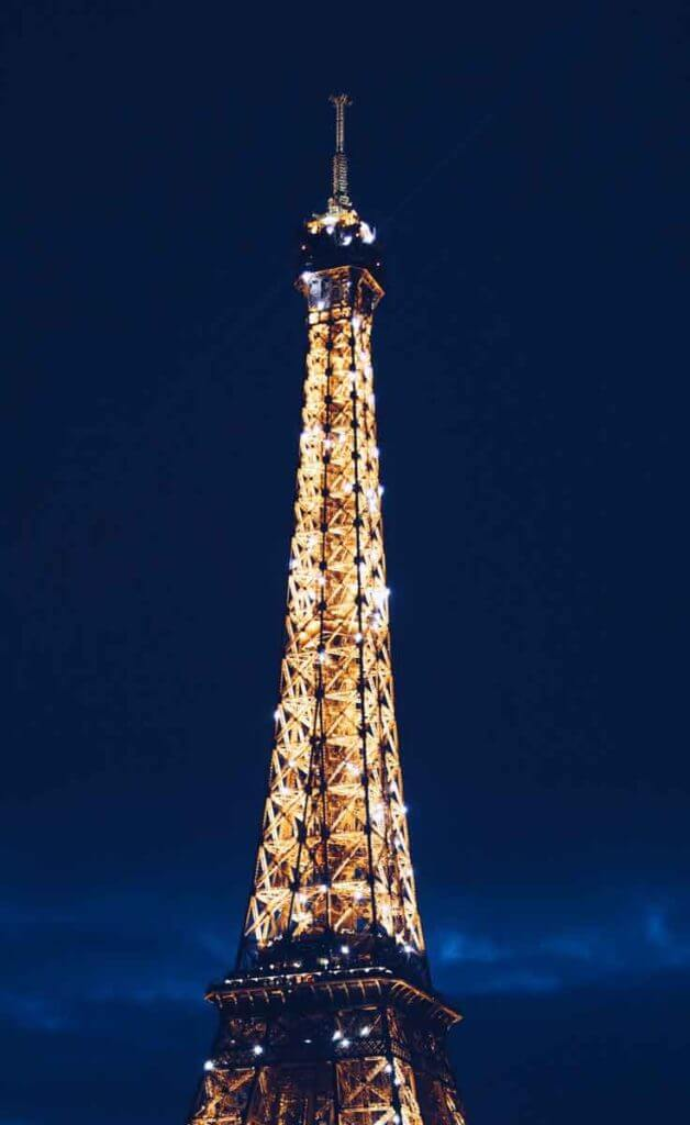 Close up photograph of the top of the Eiffel Tower in Paris, France light up at night.